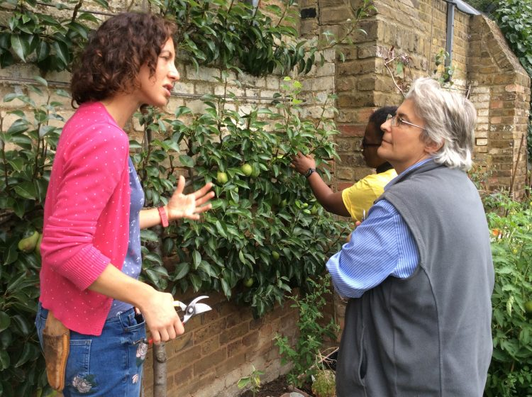 student gesticulating to another student, holding secateurs